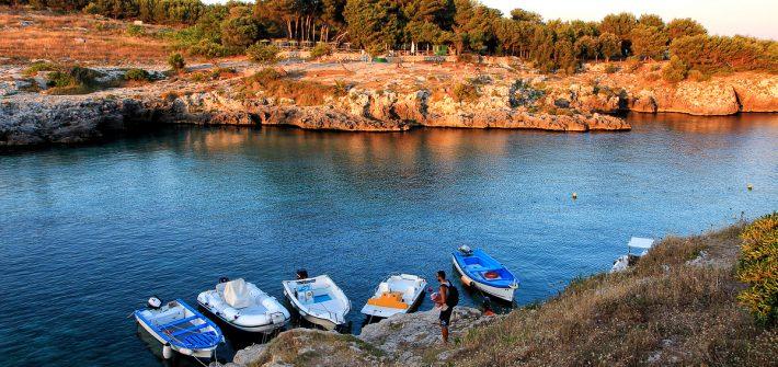 Delle barche legate sugli scogli di Porto Badisco al tramonto