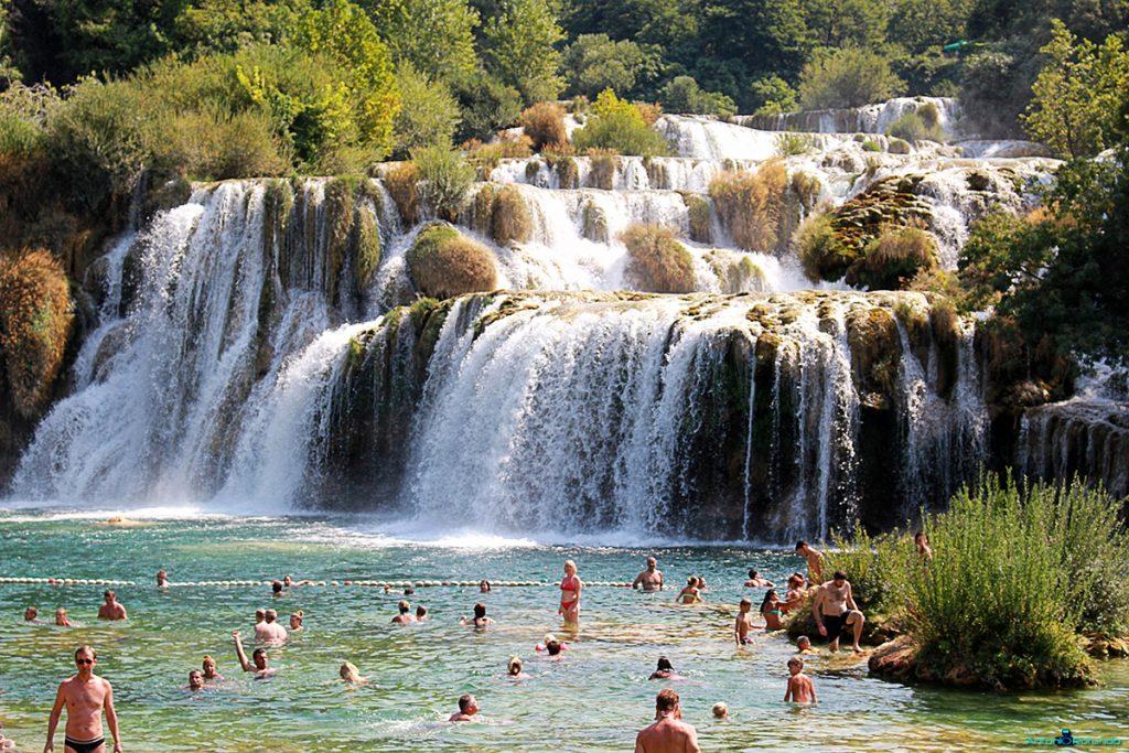 Persone che fanno il bagno sotto la cascata del parco di Krka
