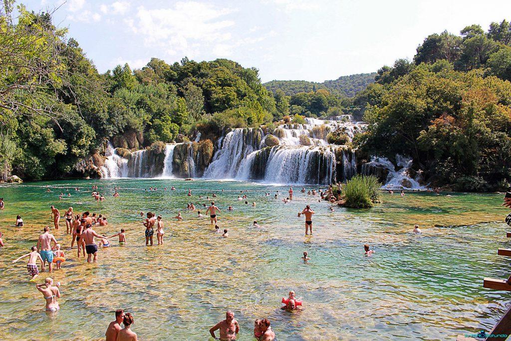 Persone che fanno il bagno sotto le cascate del parco di Krka
