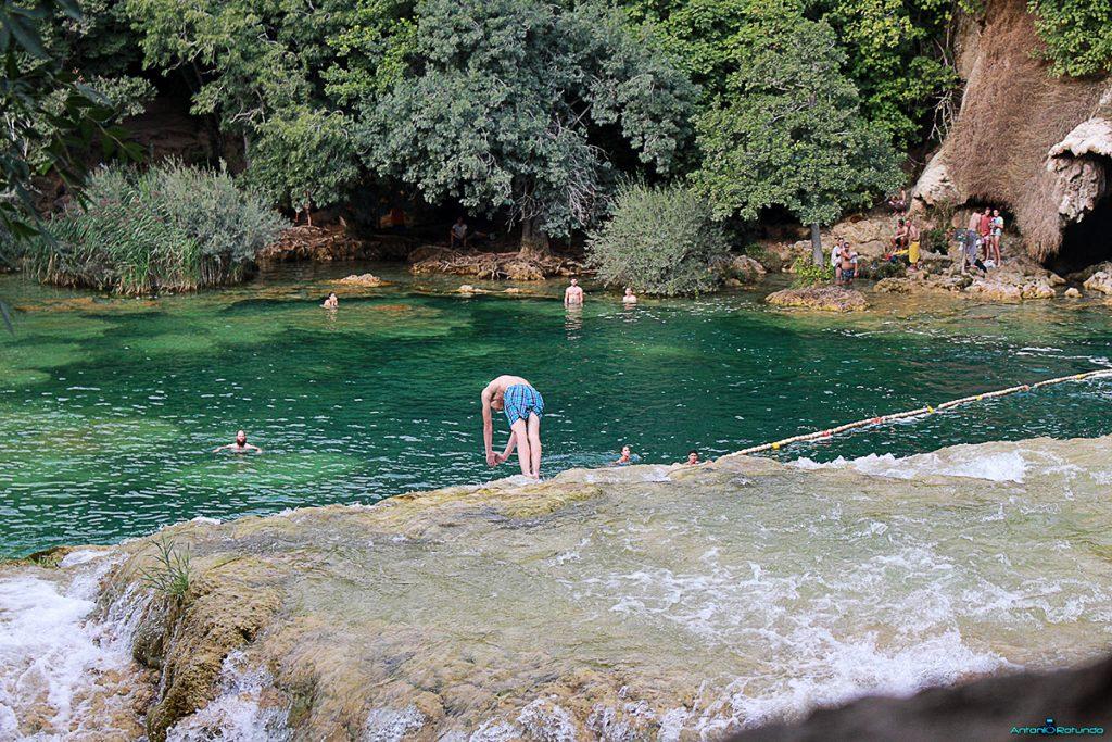 Ragazzo che si tuffa dalla cascata del parco di Krka