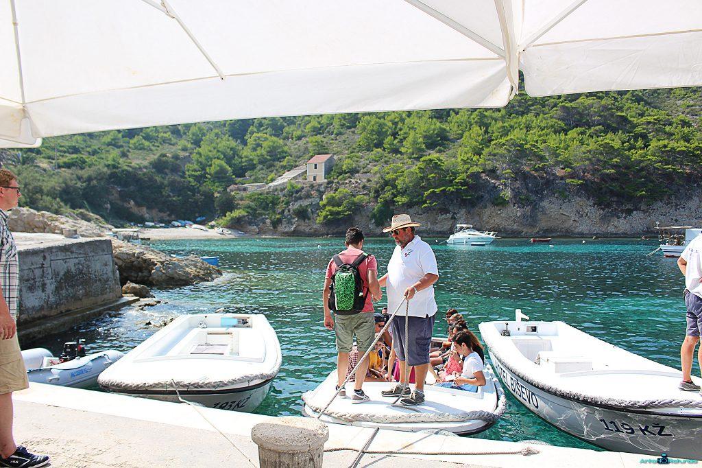 Durante il mio viaggio in Croazia, un uomo con un cappello aiuta un ragazzo a salire su una barca