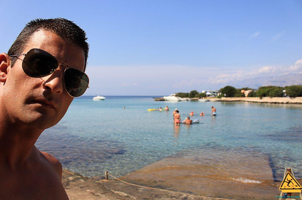 un mio selfie con alle spalle una caletta con dei ragazzi che fanno il bagno durante il mio viaggio in Croazia