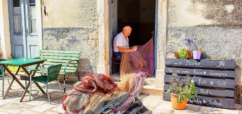 un pescatore conosciuto durante il mio viaggio in Croazia che ripara la sua rete da pesca