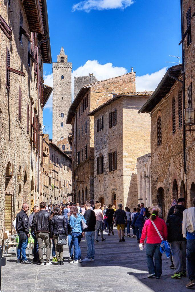 una strada del centro con persone che passeggiano, ecco cosa vedere a San Gimignano