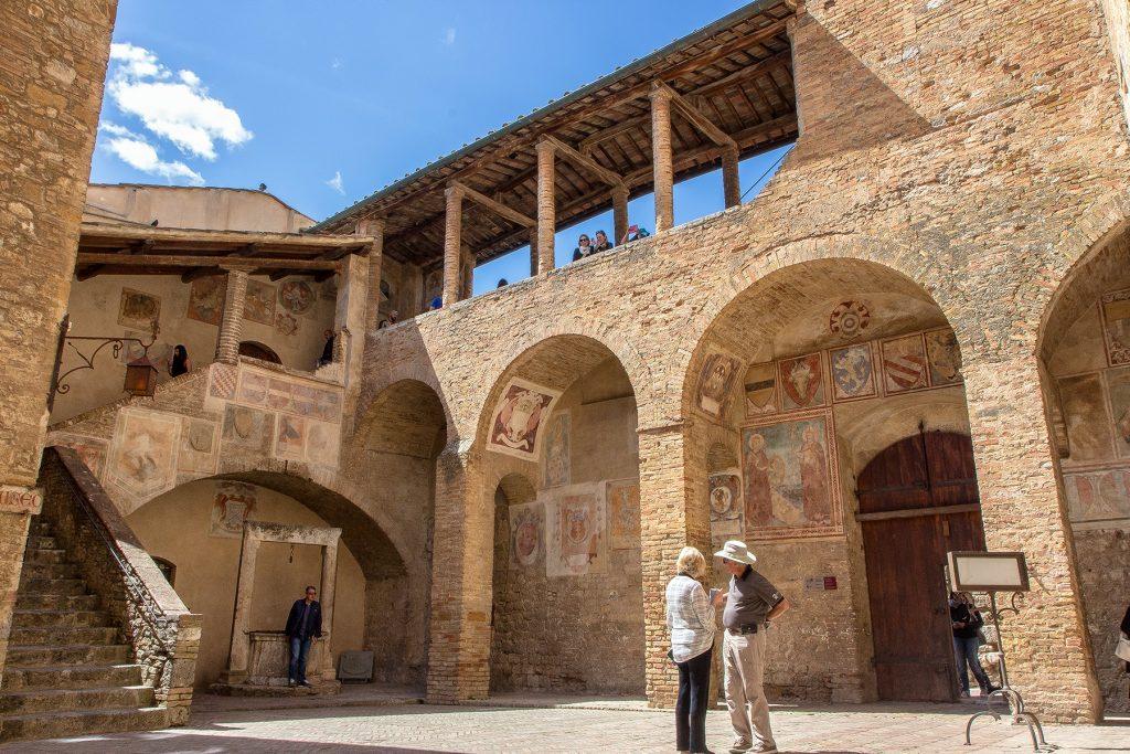 interno del cortile del Palazzo Comunale, con una cisterna sullo sfondo e una scala. Ecco cosa vedere a San Gimignano in piazza Duomo.