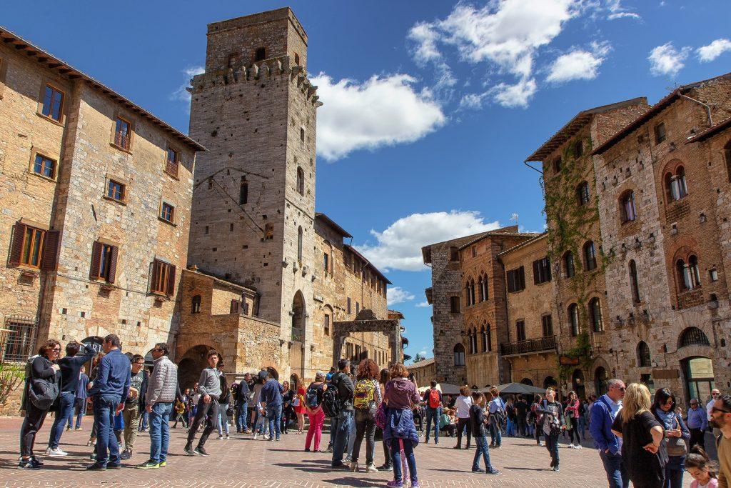 una piazza gremita di persone che osservano cosa vedere a San Gimignano