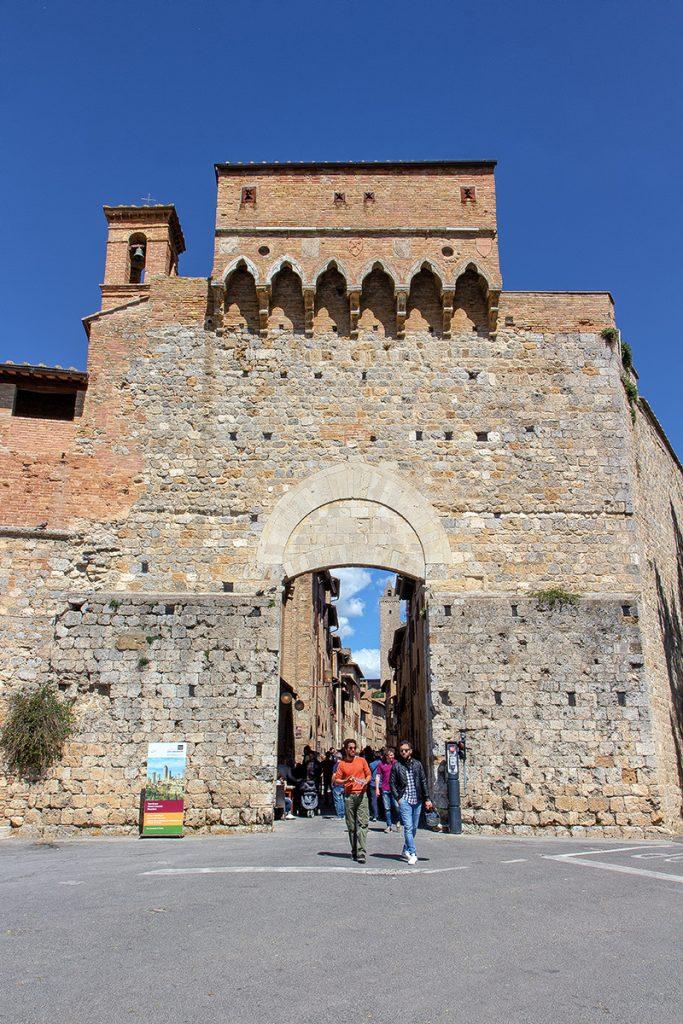 porta medievale con persone a piedi che la attraversano, ecco cosa vedere a San Gimignano