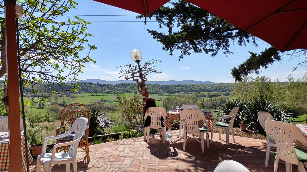 Scorcio della vista sulla Val D'elsa, con dei tavolini e una ragazza che prende il sole. Meta ideale su cosa vedere a San Gimignano
