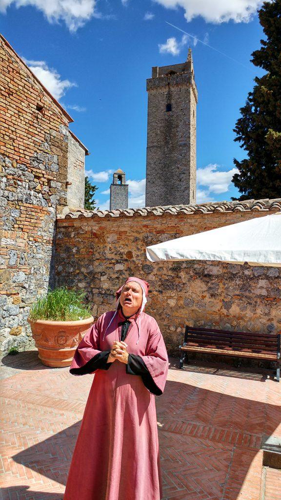 uomo che recita una poesia vestito da Dante Alighieri, ecco cosa vedere a San Gimignano.