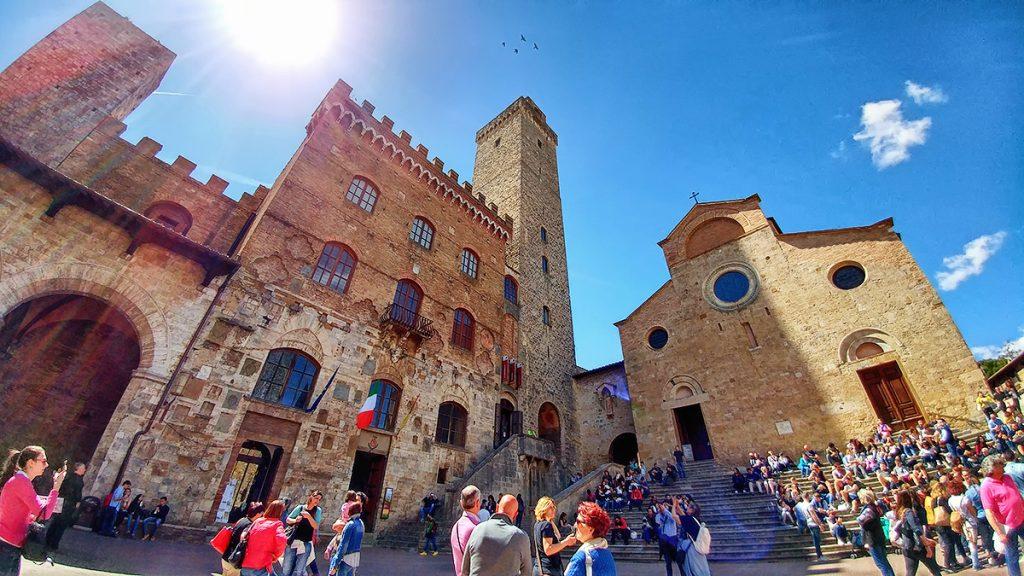 una piazza con scalinata di una chiesa e torre con un orologio, ecco cosa vedere a San Gimignano