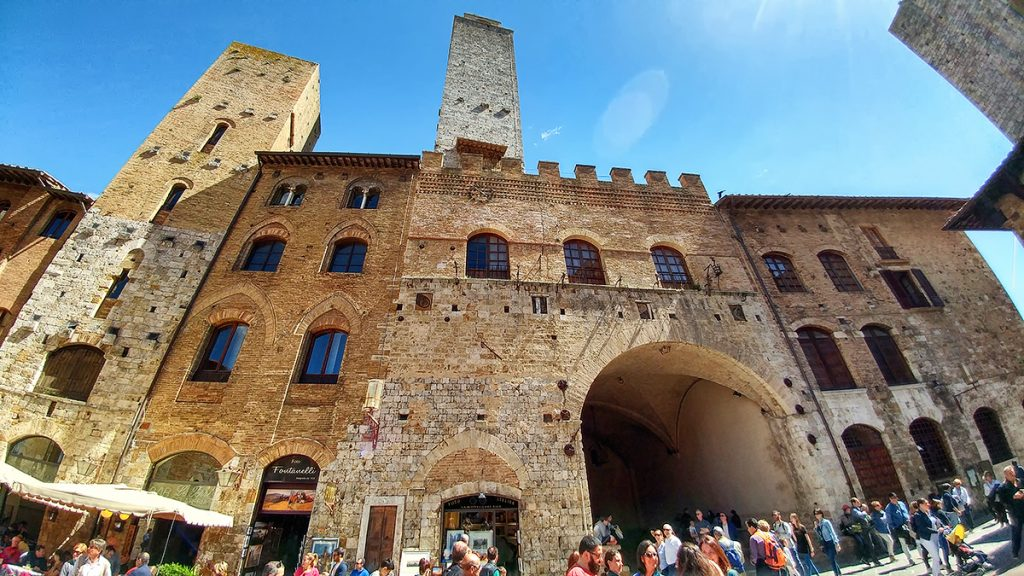 un palazzo storico con un arco e una torre sulla sommità, ecco cosa vedere a San Gimignano