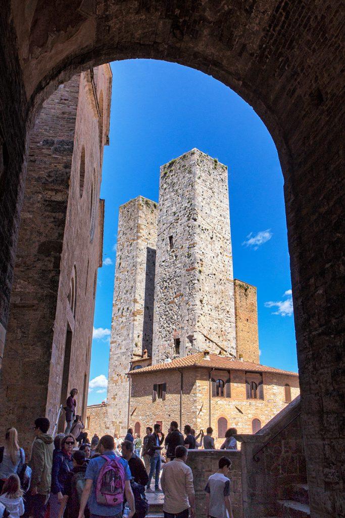 un arco con due torri medievali sullo sfondo, ecco cosa vedere a San Gimignano