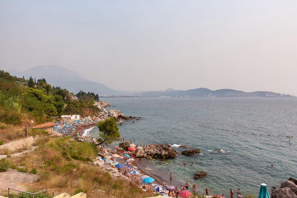 Uno scorcio di una spiaggia con ombrelloni e sdraio in riva al mare durante il viaggio in Montenegro