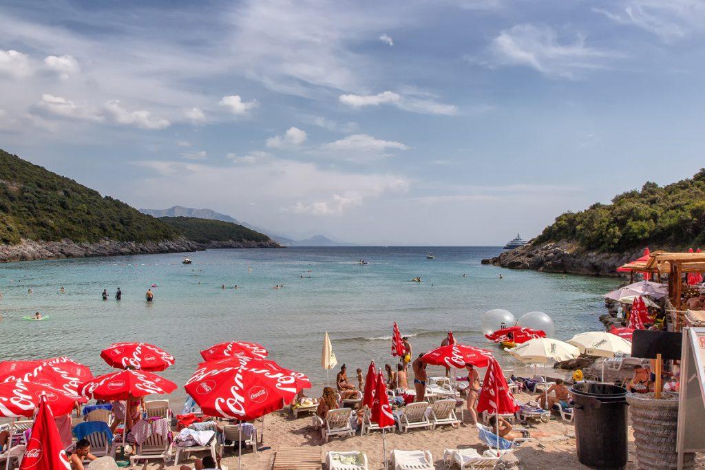 una spiaggia con ombrelloni rossi e un mare limpido, scorcio della spiaggia trsteno durante il viaggio in Montenegro