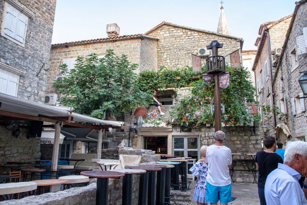 un locale con dei tavolini all'esterno e una coppia che si abbraccia durante il nostro viaggio in Montenegro