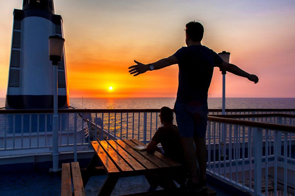 due ragazzi ammirano il tramonto sul ponte della nave, durante il viaggio in Montenegro