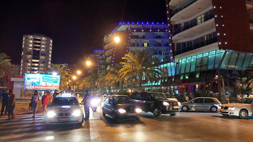 la città di Budva illuminata di notte, con grattaciele e macchine che sfrecciano durante il viaggio in Montenegro