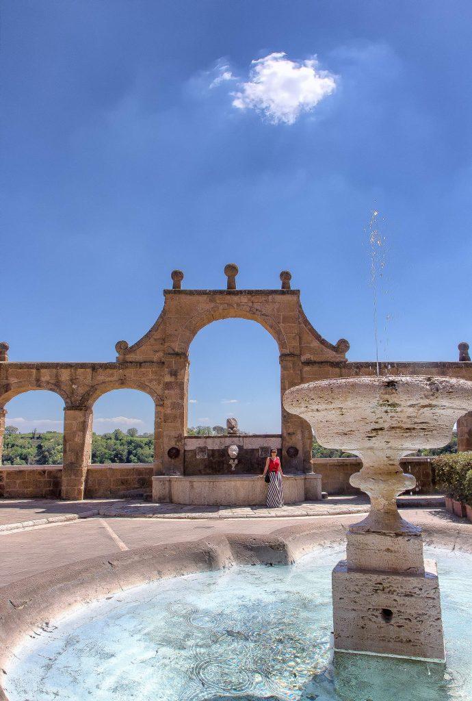 una fontana in primo piano con l'acquedotto di Pitigliano sullo sfondo, ecco cosa vedere in Maremma