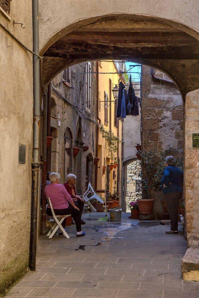 Delle vecchiette che chiacchierano tra di loro sedute all'aperto