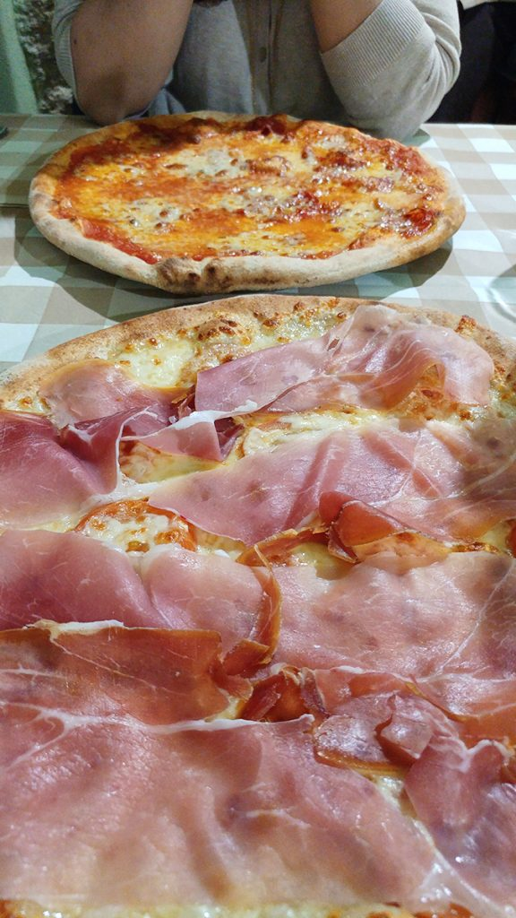 Due pizze su un tavolo in una locanda di Pitigliano, ecco cosa vedere in Maremma