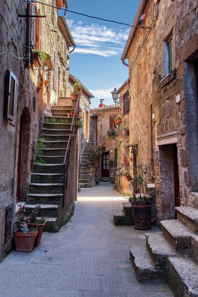 Un vicolo all'interno di Pitigliano pieno di vasi fioriti e piccole scalinate, ecco cosa vedere in maremma
