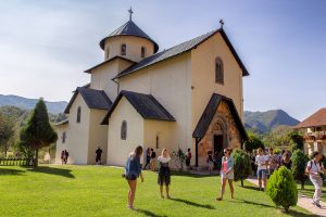 chiesa ripresa di lato con tre ragazzi che cammina davanti, ecco cosa vedere durante le vacanze in montenegro