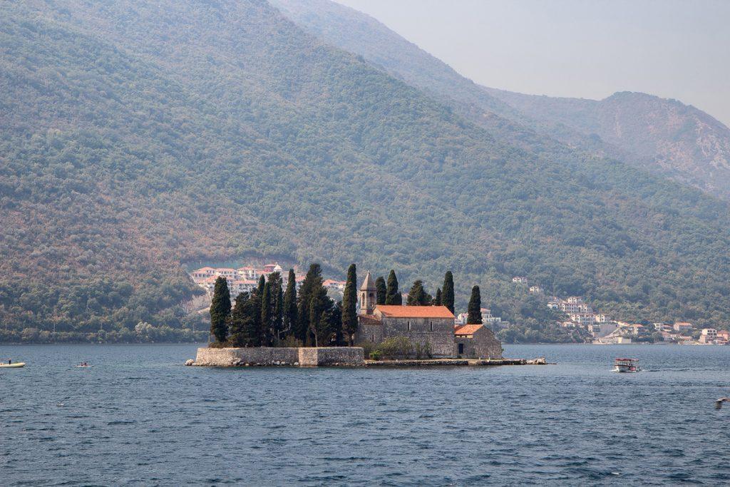 isola di San Giorgio con sopra un'abbazzia benedettina e dei cipressi. vista durante il tour nella baia di Kotor