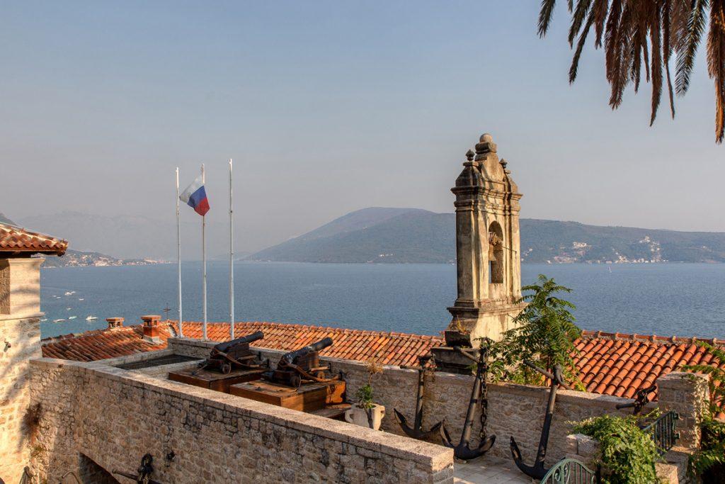 veduta dal Forte Mare sulla Baia di Kotor con dei canoni e una bandiera che sventola
