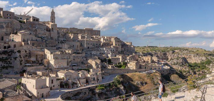 La città di Matera sullo sfondo e due ragazzi che scendono una scalinata in primo piano. Visitare Matera in un giorno