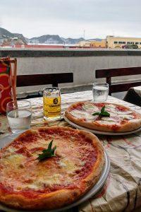 Arrivare a Ponza e andare a mangiare nella pizzeria rosticceria ponzese sul via del corso con vista mare