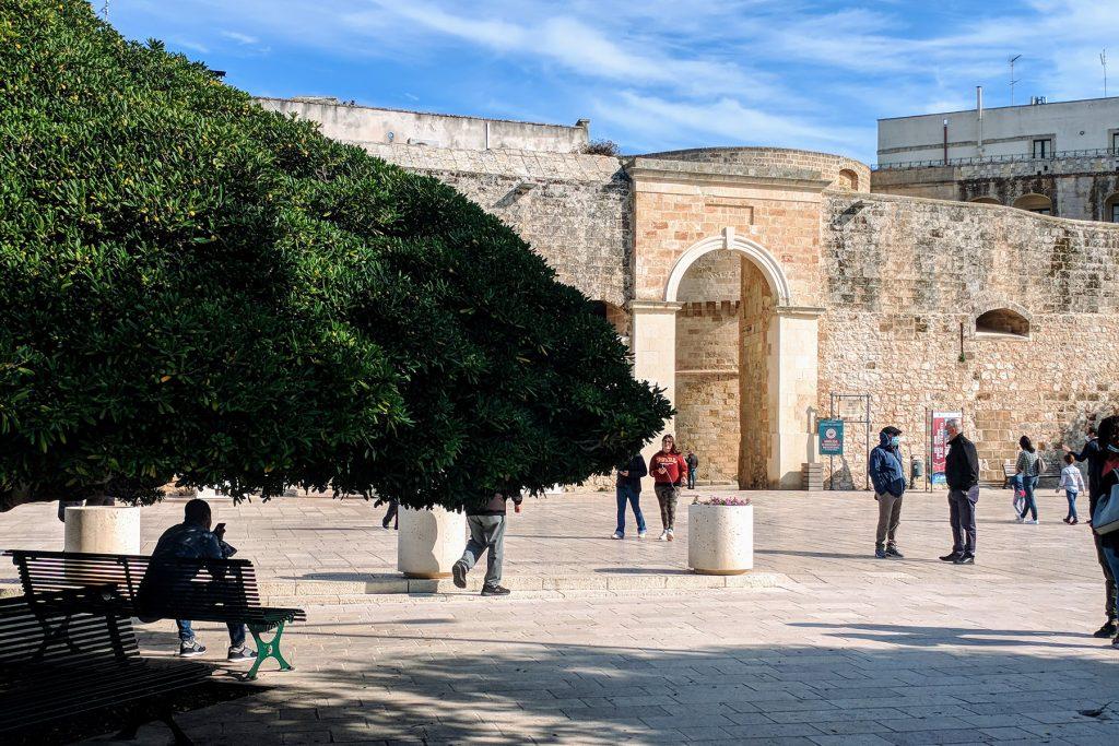 Vista della Porta Alfonsina di Otranto da sotto un albero con panchina